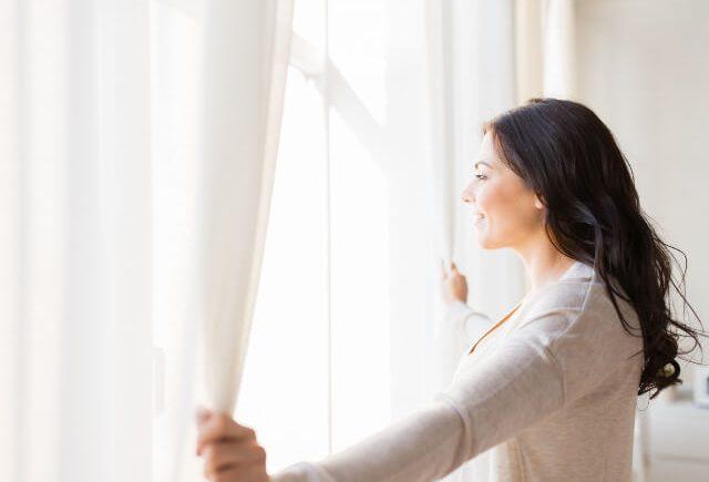 カーテンを開けて陽の光を浴びる女性